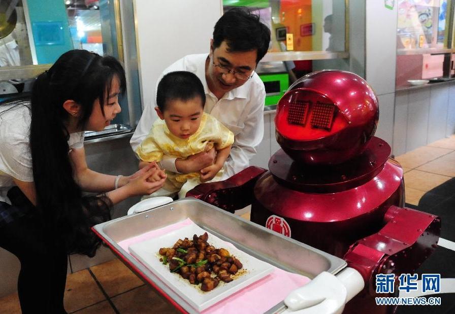 客人带着孩子在餐厅内观看送菜机器人