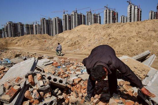 李瑞(音译)在聊城被拆的村庄捡拾建筑材料。他三年前还是一个农民,随后当地地府将他的村庄夷为平地,建设城市发展区。